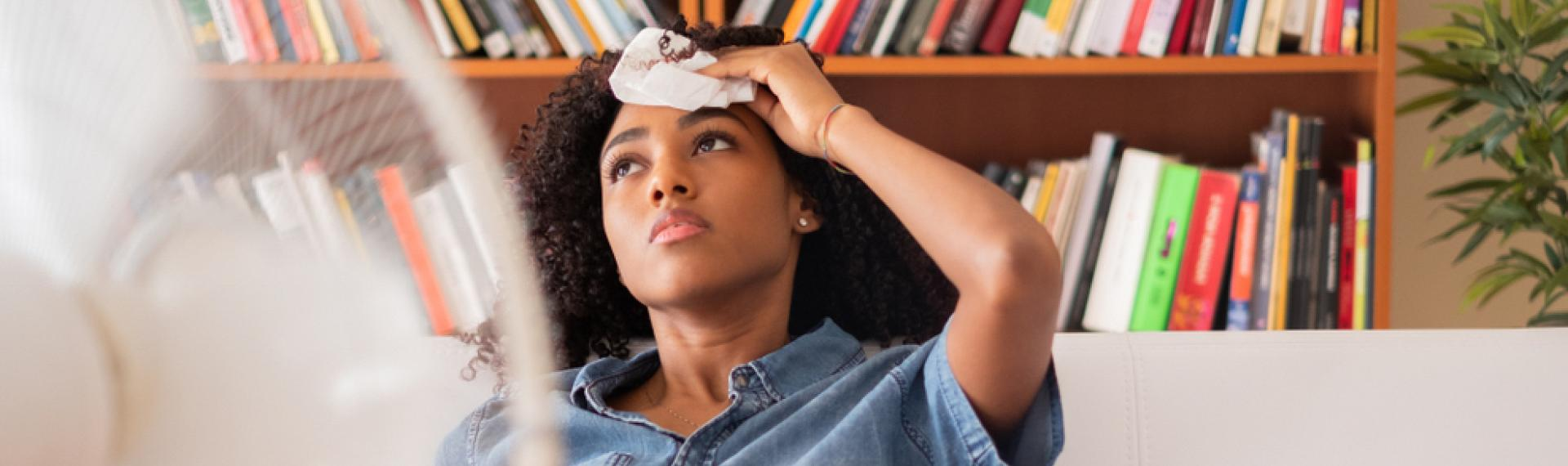 Woman Warm In Room Sitting In Front Of Fan Holding Cold Wash Cloth On Her Forehead
